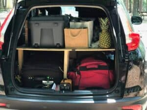 Car camping set up with shelf and sections for camping supplies